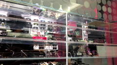People picking a sunglasses on display frame inside Burnaby shopping mall - stock footage