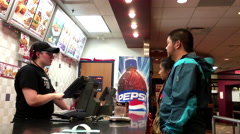People considering to order food inside KFC chicken restaurant Stock Footage