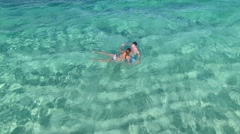 Aerial view of couple swimming in caribbean sea Stock Footage