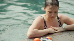 A woman at the edge of a pool looking at pool toys, and then returning to swim Stock Footage