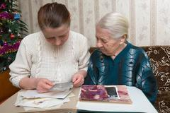 Two women consider old photos in which they are represented at young age Stock Photos