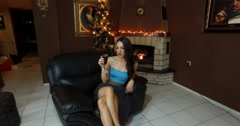 Sexy brunette young woman drinking wine by the fire place Christmas Stock Footage