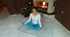 Crane Shot Of Woman Practicing Yoga In Front Of Fire Place At Home 2 Stock Footage
