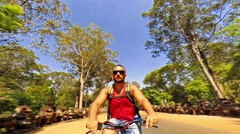 Man on a bicycle in a forest in Seam Reap - stock footage