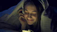 Girl in bed with a headphones on listening to the music Stock Footage