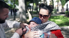 Young parents wearing baby sling in the city park Stock Footage