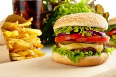Cut image of big cheeseburger with french fries and glass of cola on wooden b Stock Photos