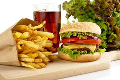 Cut image of big cheeseburger with french fries and glass of cola on wooden b - stock photo