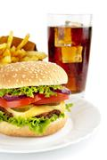 Cut image of big cheeseburger with french fries and glass of cola on plate - stock photo