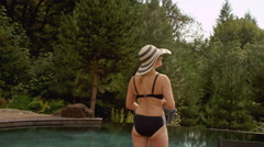 An older woman standing next to a pool looking out at the mountain view - stock footage