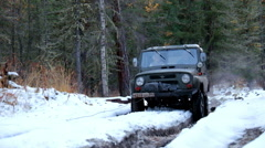 Russian off-road vehicle Uaz Patriot on winter road in siberian Altay forest Stock Footage