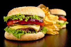 Big two cheeseburgers with french fries on black background Stock Photos