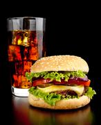 Big single cheeseburger with glass of cola on black wooden desk - stock photo