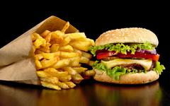 Big single cheeseburger with french fries on black wooden table - stock photo