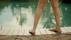 An older woman testing the water in a pool with her toes, in slow motion Stock Footage