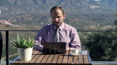 Young businessman signing documents sitting by table at terrace in the country Stock Footage