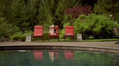 An older woman at a pool gets out of her chair to test the water with her toes Stock Footage