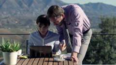 Successful business couple with laptop computer on terrace in the country Stock Footage