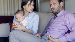 Young husband giving her wife money and playing with his child at home - stock footage