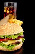 Cut image of big cheeseburger with french fries and glass of cola on black wo Stock Photos