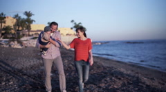 Young happy couple s walking with small baby on the beach Stock Footage