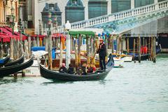 Gondola with tourists in Venice, Italy - stock photo