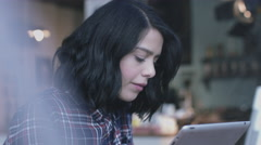 Young adult woman working on digital tablet in café window Stock Footage
