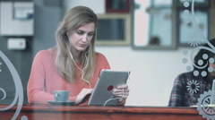 Female in coffee shop working on digital tablet Stock Footage
