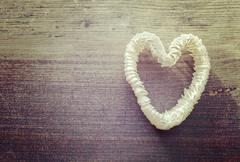Vintage stylized heart made of shells on wooden background. - stock photo