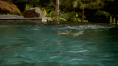 An older woman swimming peacefully in a pool emerges and smiles Stock Footage