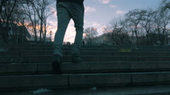 Young man climbing up the steps on city centre background, 4k Stock Footage