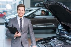 Sale assistant working in auto salon - stock photo
