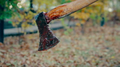 Blood running down murder weapon, maniac kills victim with axe, terrible crime Stock Footage
