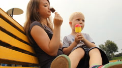 Happy young mother with her son in summer park eating ice cream on a bench Stock Footage