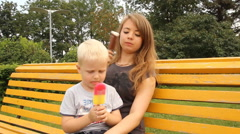Happy young mother with her son in summer park eating ice cream on a bench - stock footage