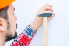 Pleasant man knocking in the nail - stock photo