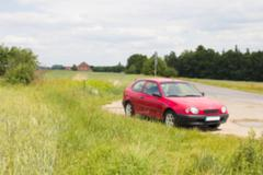 Stock Photo of Blurred photo of car standing next to the meadow