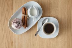 Cup of coffee, white rose, cinnamon on a wooden background - stock photo
