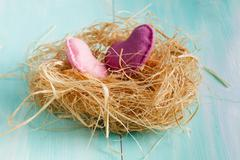 Two red hearts in a bird nest on wooden board Stock Photos