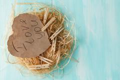 Two pink paper hearts in a small nest on wooden background. - stock photo