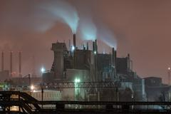 Power station with steam cloud blown by the wind in a cold starry winter nigh - stock photo