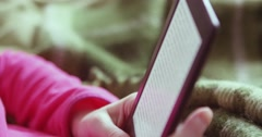 Girl reads e-book / e-reader. Girls holds e-reader. Close up e-reader. Woman Stock Footage
