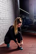 Fitness girl tying shoelace in the gym Stock Photos