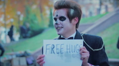 Guy in zombie suit smiling, offering free hugs to people in street, freak show Stock Footage
