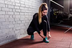 Attractive girl ties the laces on sneakers - stock photo
