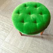 Green velvet stool on tiled floor Stock Photos