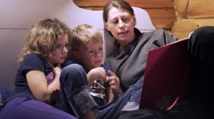 A woman reading a book for two kids Stock Footage