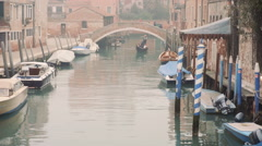 Venetian gondolier punting gondola through green canal waters of Venice, Italy Stock Footage