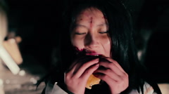 Stock Video Footage of Fastfood addict female zombie eating burger, scary creature enjoying lunch time