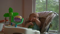 Baby Boy Sitting In High Chair At Meal Time Stock Footage
